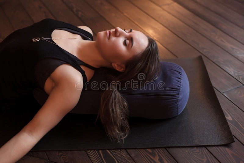 Girl relaxing after a yoga class. Woman resting after a yoga class in shavasana. Under back her bolster for spine therapy royalty free stock photo