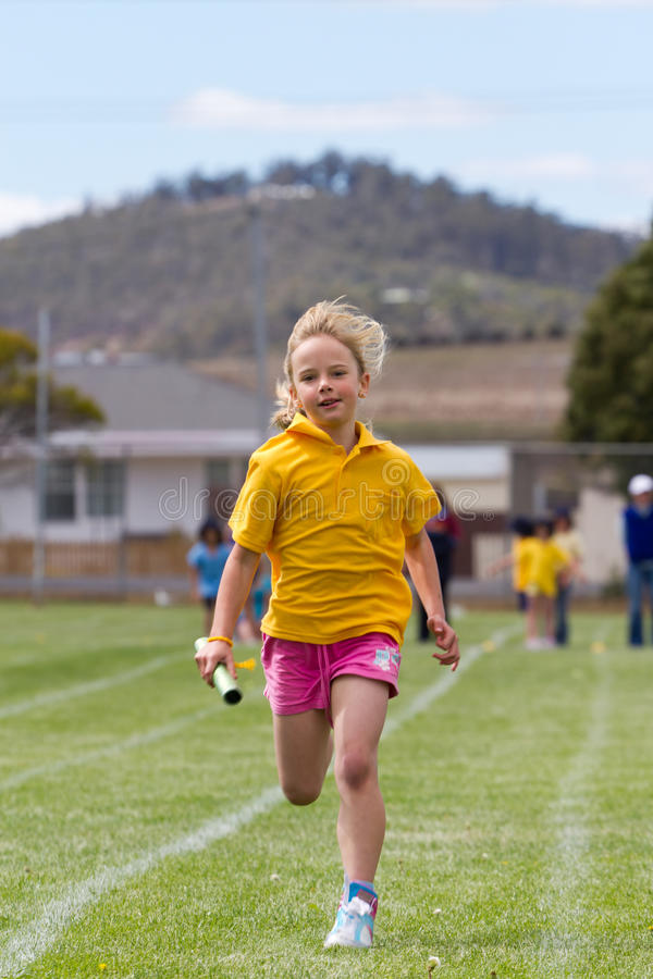 Girl in relay race royalty free stock image