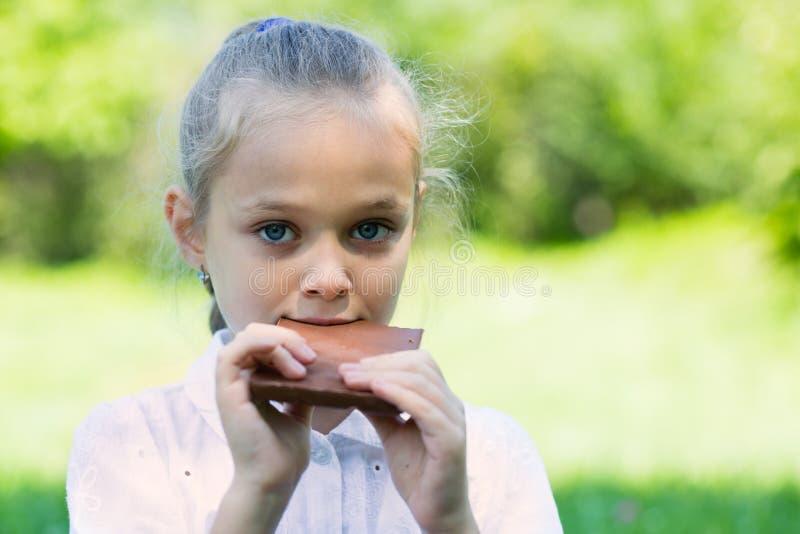 Girl with relish eating a chocolate bar. Girl with relish eating a chocolate bar outdoors stock image