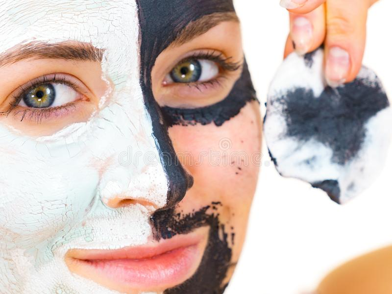 Girl remove black white mud mask from face. Woman with clay carbo black mask on one half face and white mud on second half. Girl removing cosmetic scrab with stock images