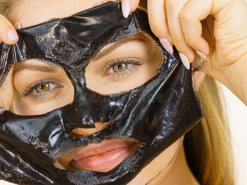 Girl removes black mask from face stock image