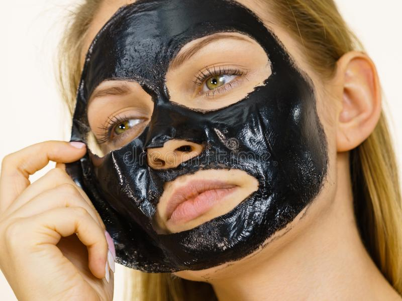 Girl removes black mask from face stock images