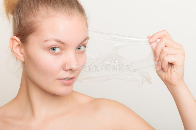 Girl removing facial peel off mask stock image
