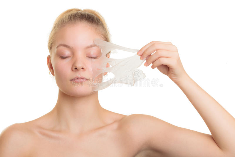 Girl removing facial peel off mask. Beauty skin care cosmetics and health concept. Closeup young woman face, girl removing facial peel off mask isolated on white royalty free stock image
