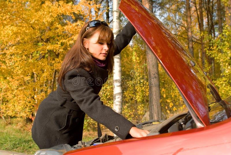 Girl repairs the car motor stock photography
