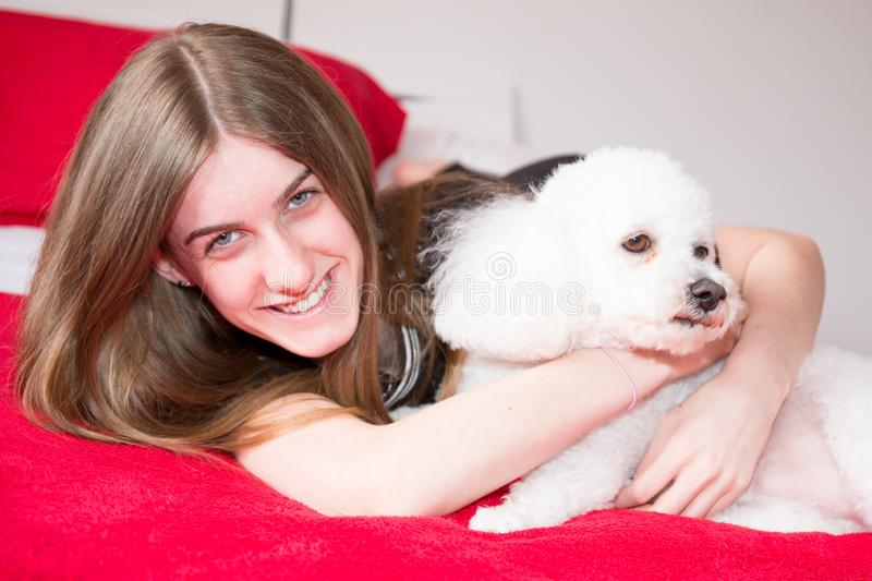 Girl is resting on bed with poodle dog on bed at home stock image