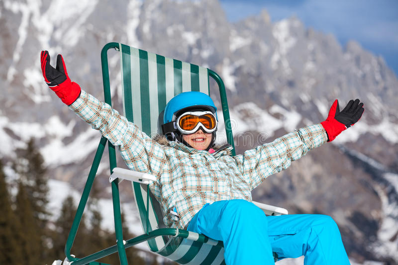 Girl resting in a deckchair. Girl sunbathing in a deckchair on the side of a ski slope stock photo