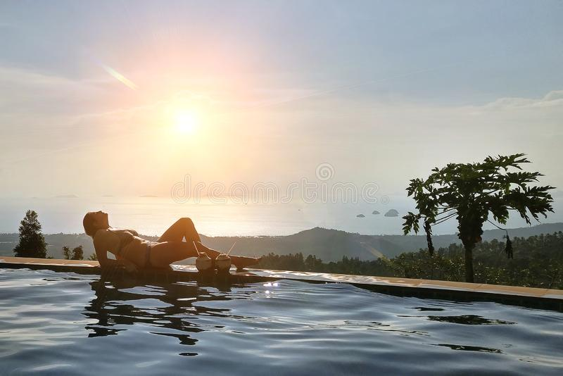 The girl is resting on the edge of the infinity pool. overlooking the tropical jungle and the beach. Near two coconuts with royalty free stock photo