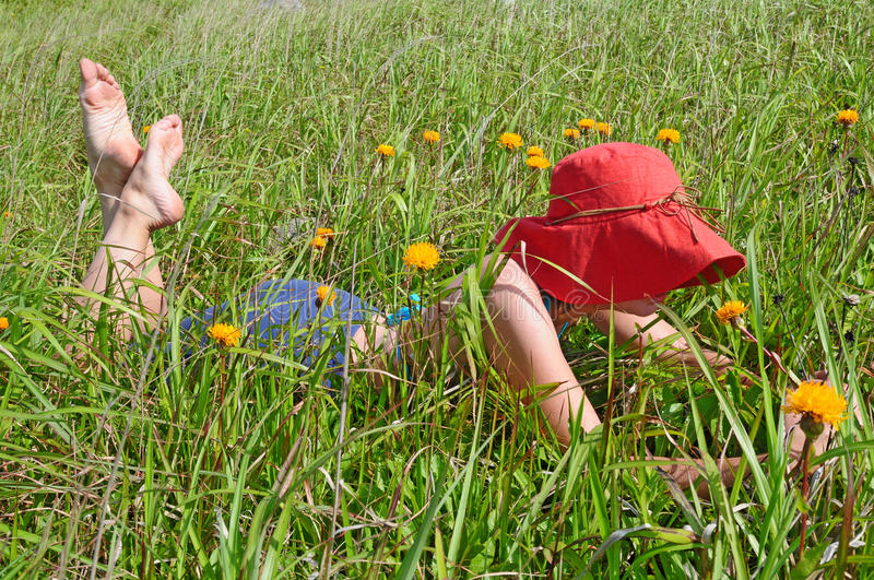 Girl resting on the green meadow with flowers royalty free stock images