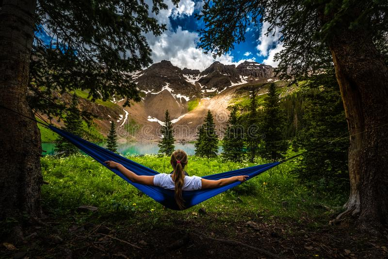 Girl rests on a Hammock looks at Dallas Peak near Lower Blue Lake Ridgway Colorado royalty free stock photo