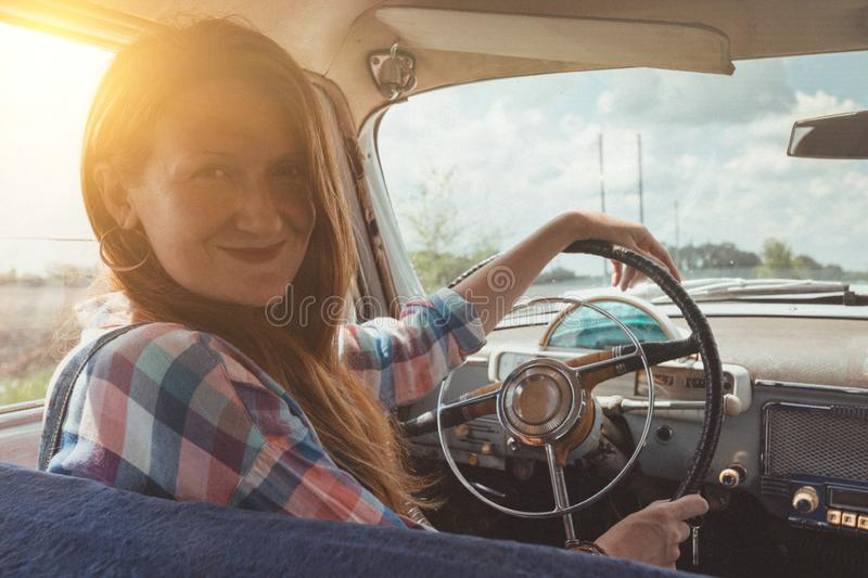 Girl and retro car. Young girl driving a retro car by the road at the fields stock photos