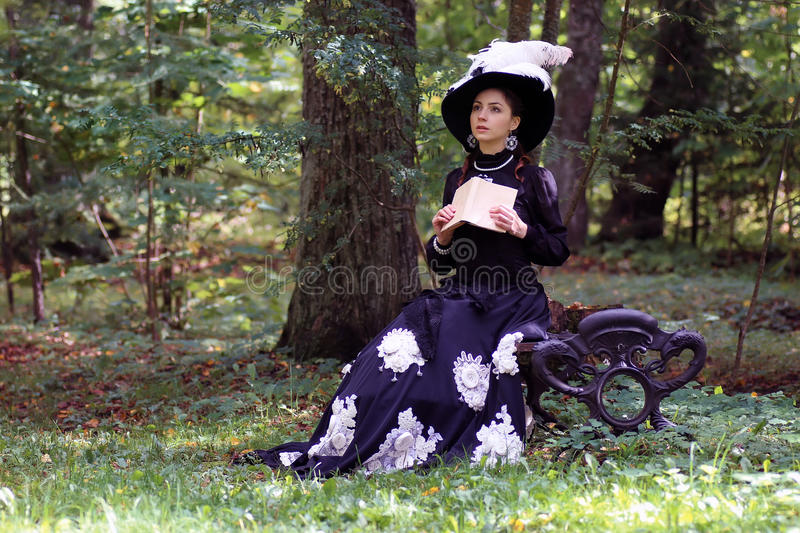 Girl in retro dress past century read letter on bench. Girl in retro dress past century read letter on the bench stock images
