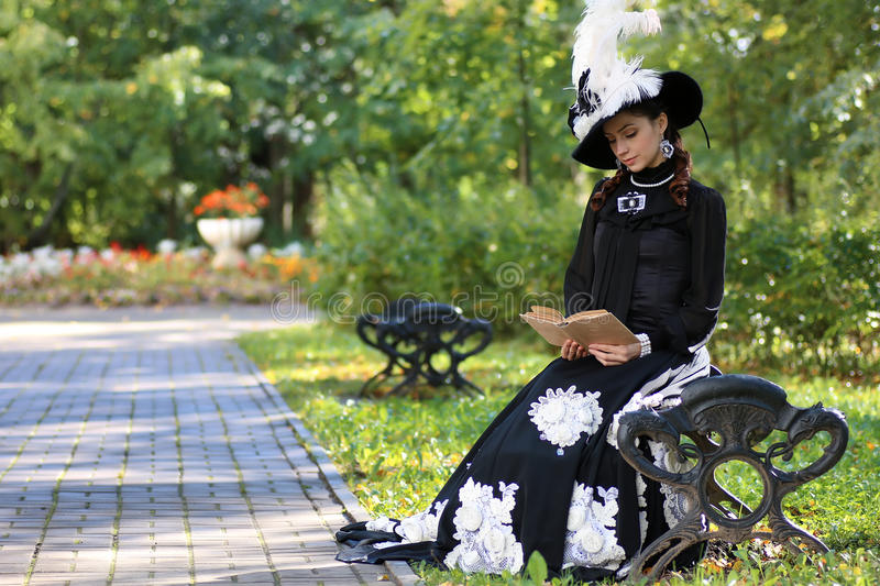 Girl in retro dress past century read letter on the bench stock images