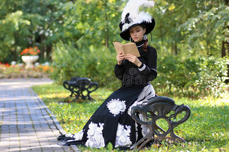 Girl in retro dress past century read letter on the bench royalty free stock image