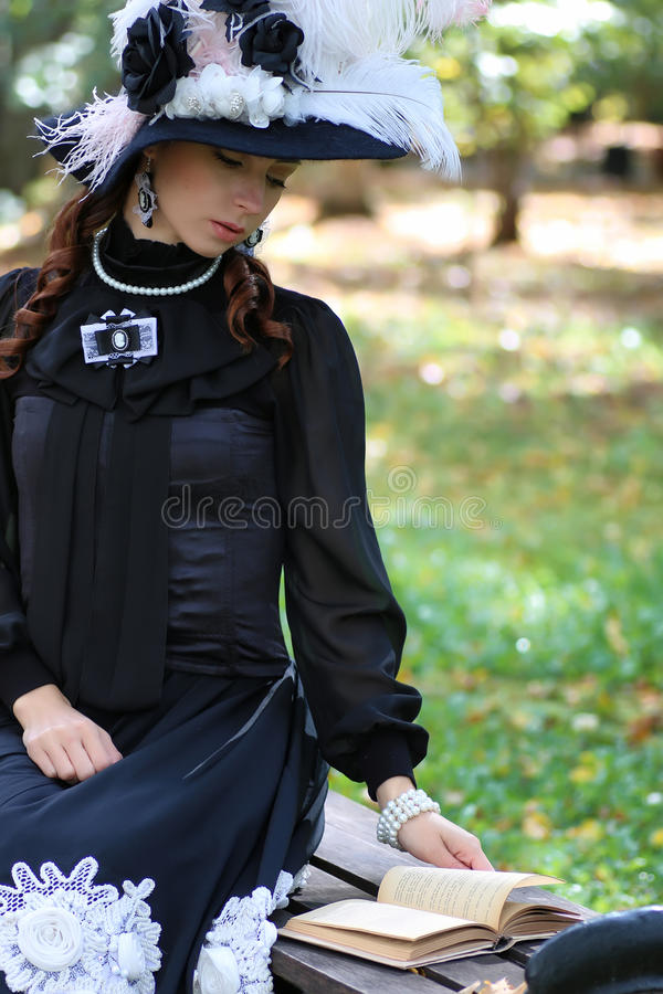 Girl in retro dress past century read letter on the bench royalty free stock photos