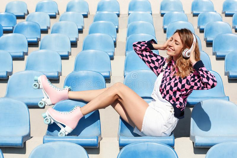 Girl with retro roller skates sitting on grandstand. Happy girl with retro roller skates sitting on grandstand royalty free stock photography