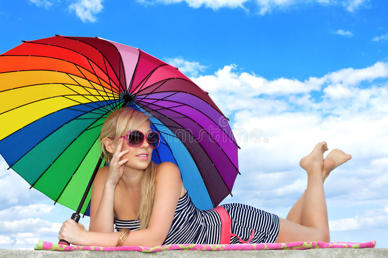 Girl in retro style by color umbrella on the beach. Glamorous girl in retro style by color umbrella on the beach royalty free stock photography
