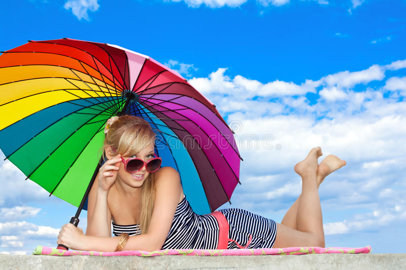Girl in retro style by color umbrella on the beach. Glamorous girl in retro style by color umbrella on the beach stock image