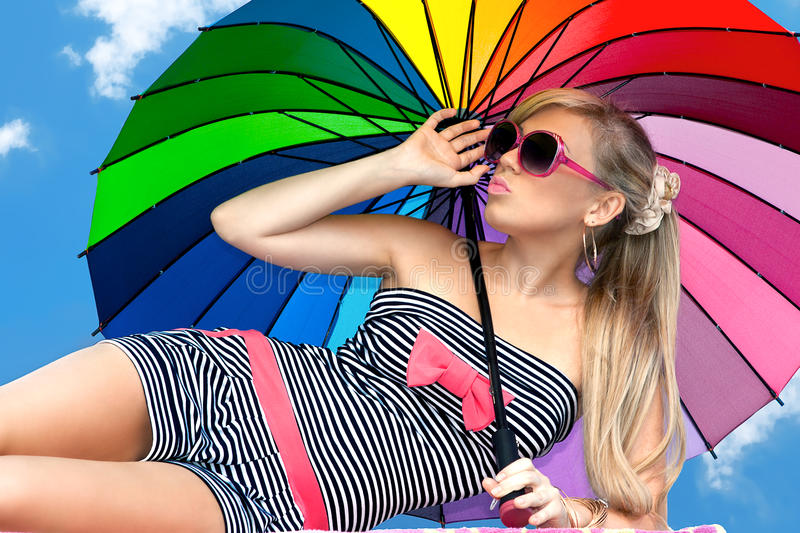 Girl in retro style by color umbrella on the beach. Glamorous girl in retro style by color umbrella on the beach royalty free stock photo