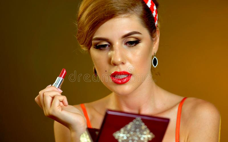 Girl in retro style paints lips royalty free stock image