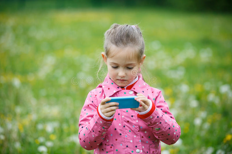 Girl reviewing photos she made with smart phone. Little girl checking and reviewing photos she made with smart phone camera, enjoying her time on a dandelion stock image