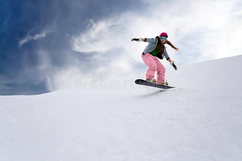 Girl rider jump on snowboard. In mountains stock photos
