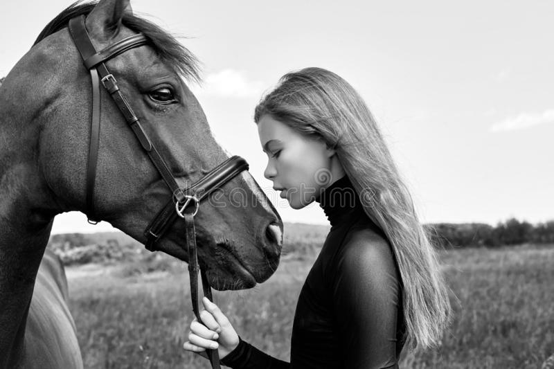 Girl rider stands next to the horse in the field. Fashion portrait of a woman and the mares are horses in the village in the grass stock photo