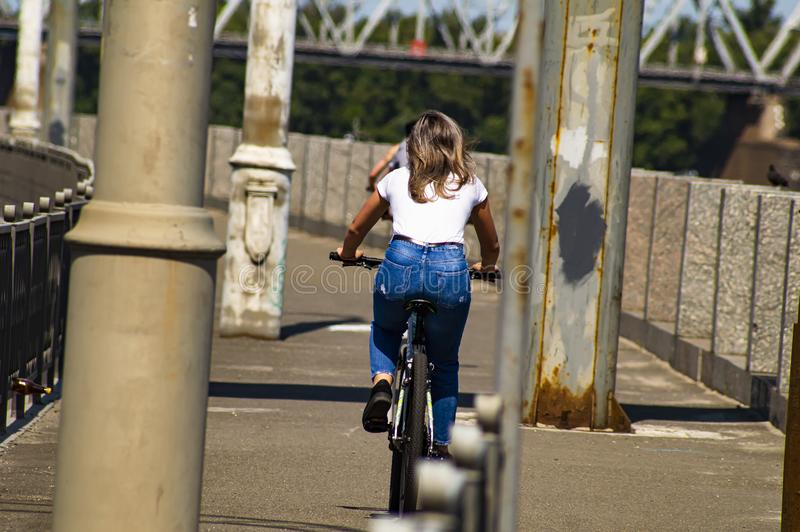 Girl rides a bicycle. Back view. Sports and recreation royalty free stock image