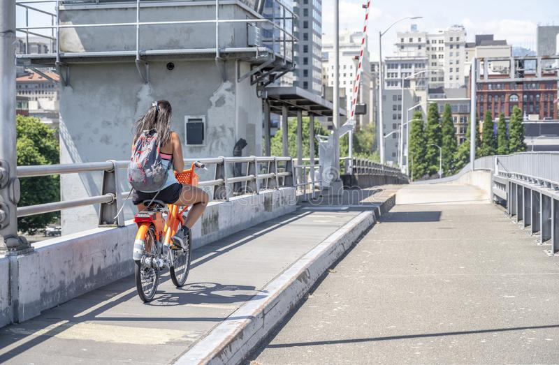 The girl rides a bicycle on the bridge and simultaneously texting on the phone stock images