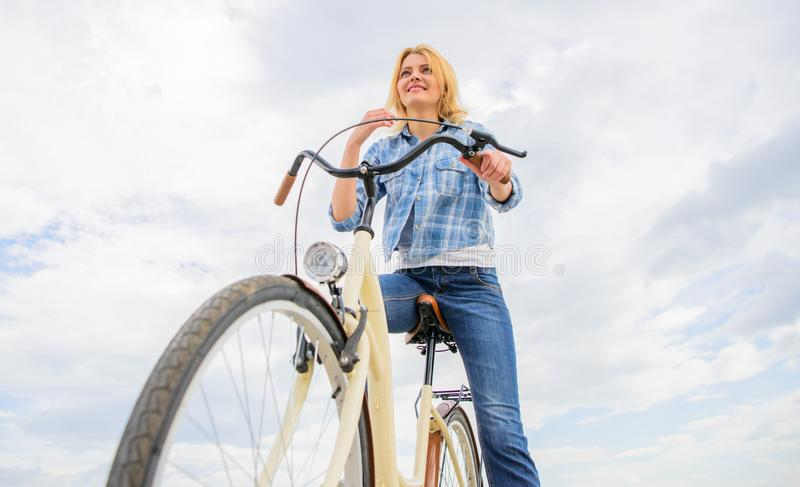 Girl rides bicycle sky background. How cycling changes your life and make you happy. Reasons to ride bicycle. Mental. Health benefits. Pedaling towards stock image