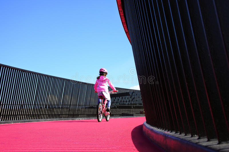 Girl rides bike on pink cycleway in Auckland. Young girl age 07 rides a bike on a bright pink cycleway in Auckland, New Zealand. Real people Copy space stock photography