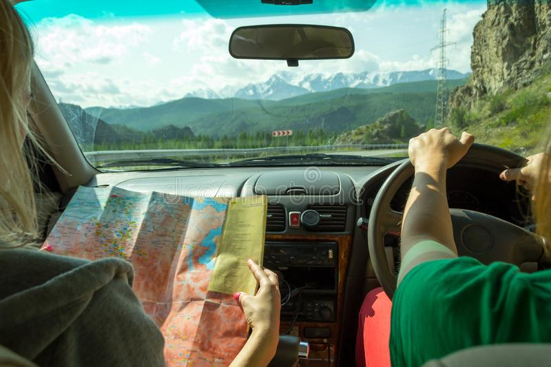 The girl rides in the car in the passenger seat and looks at the paper map looking for the desired route and indicates the road stock image
