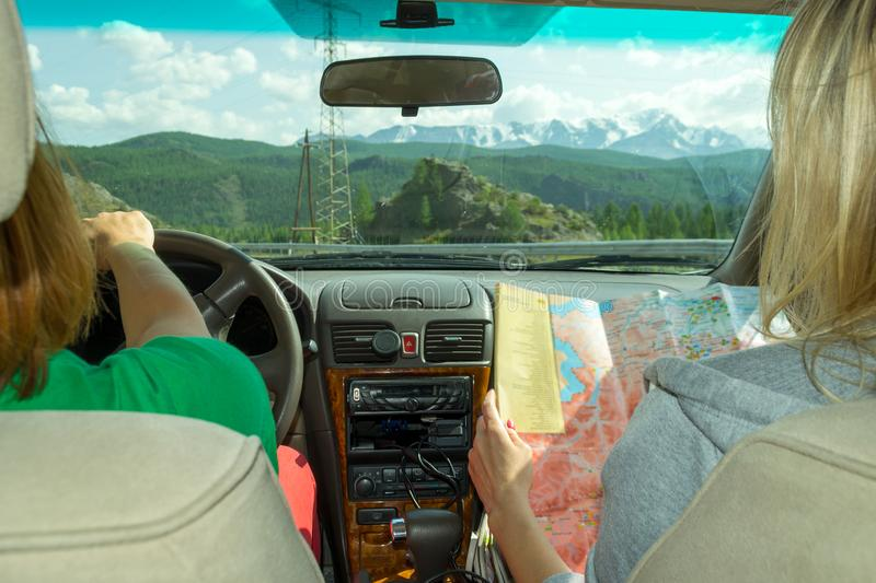 The girl rides in the car in the passenger seat and looks at the paper map looking for the desired route and indicates the road stock images
