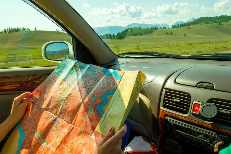 The girl rides in the car in the passenger seat and looks at the stock image