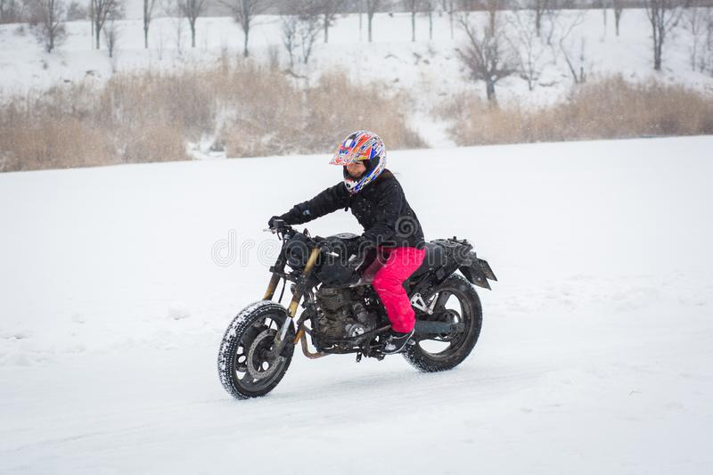 A girl rides a motorcycle on a frozen lake royalty free stock images
