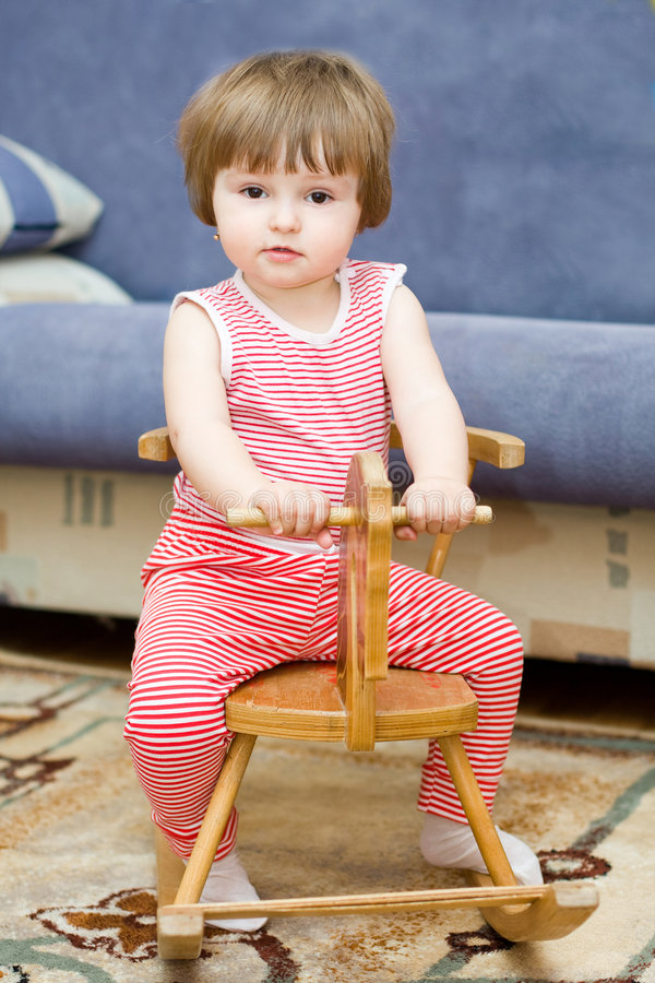 Girl rides on the toy horse stock image