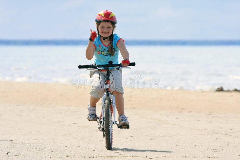 Girl riding with bicycle along the beach stock images