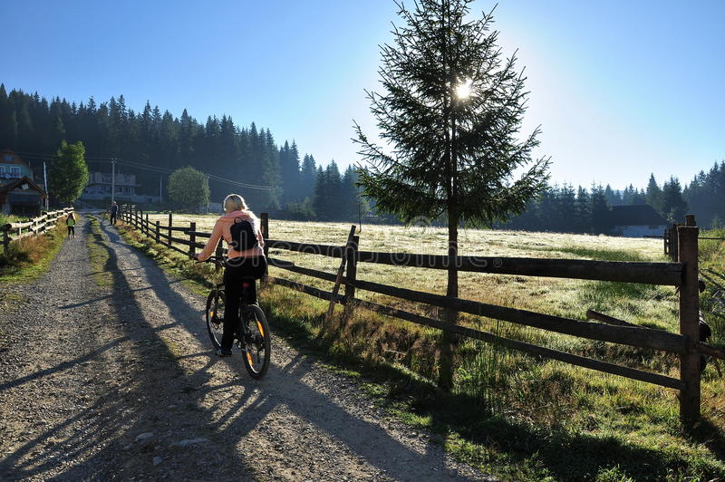 Girl riding a bicycle, beautiful nature Carpathians royalty free stock images