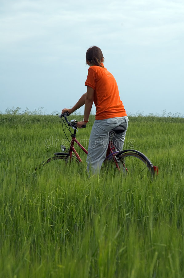 Download Girl Riding Bicycle In Green Field Vertical Stock Image - Image: 1223823