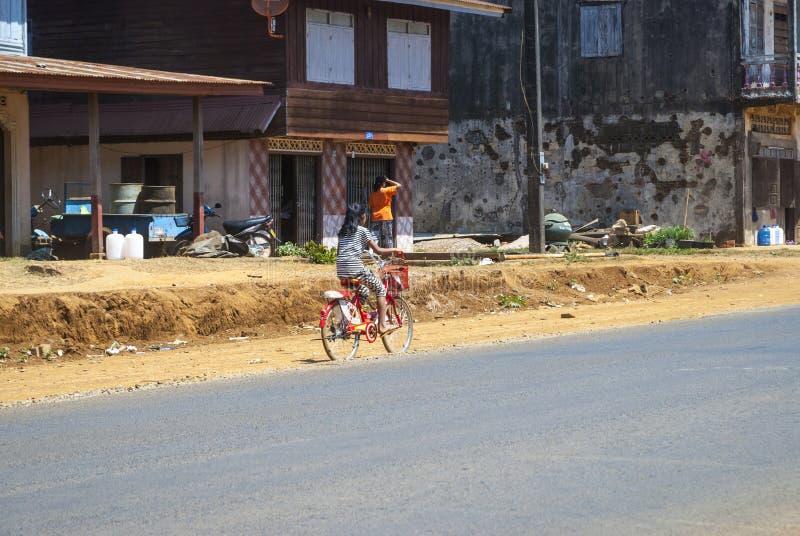 Girl riding a bicycle, Laos stock images