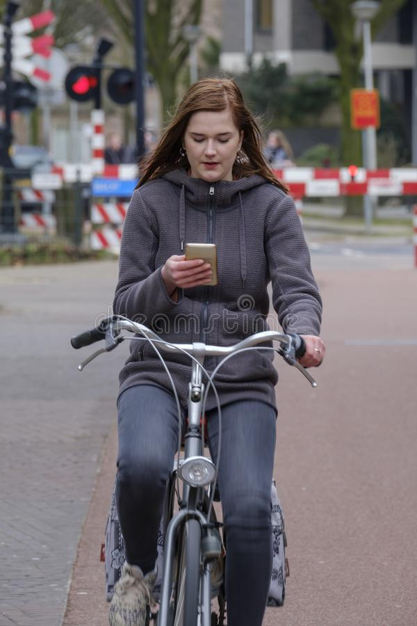 Girl riding a bike and looks at her smartphone, danger stock photo