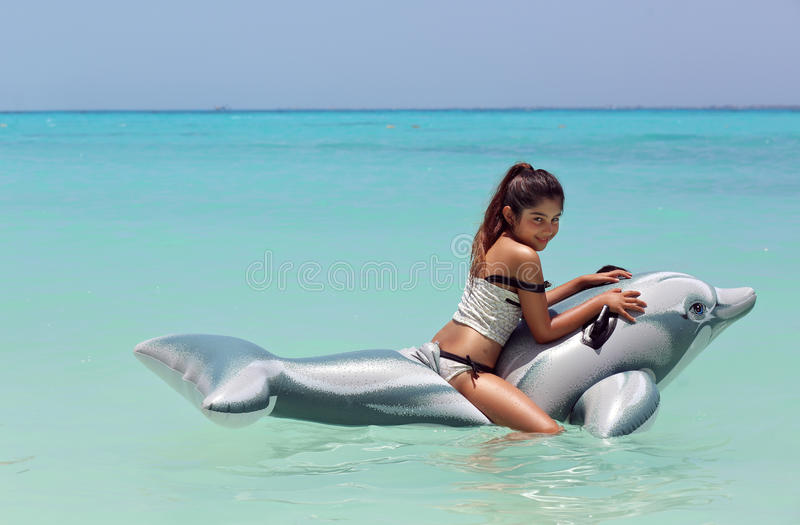 girl riding on a dolphin stock photography