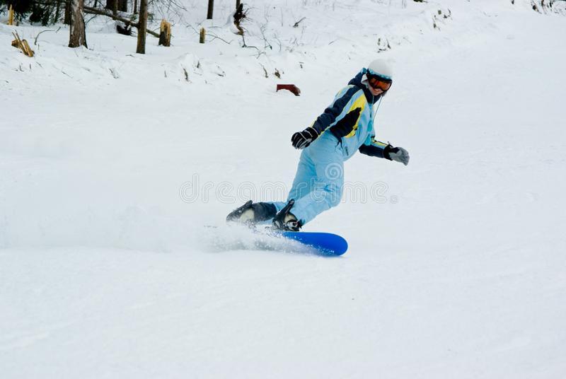 Girl riding fast on snowboard royalty free stock photography