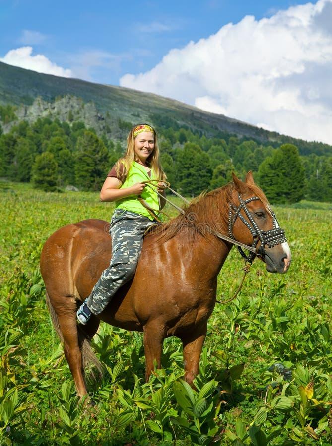 Girl riding a horse bareback. At mountains stock photo