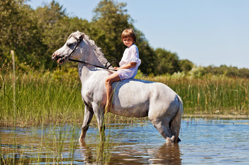 Girl riding a horse in a river. Little girl riding a horse in a river stock photo