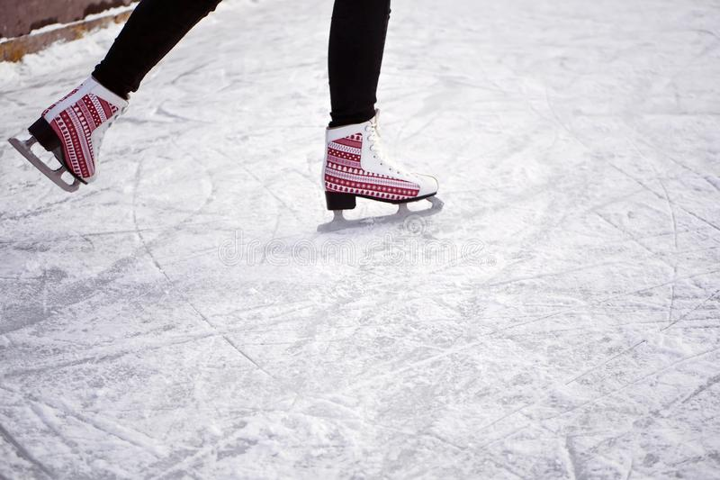 Girl riding on an ice rink. Ice and skates. Man`s feet in skates stock image