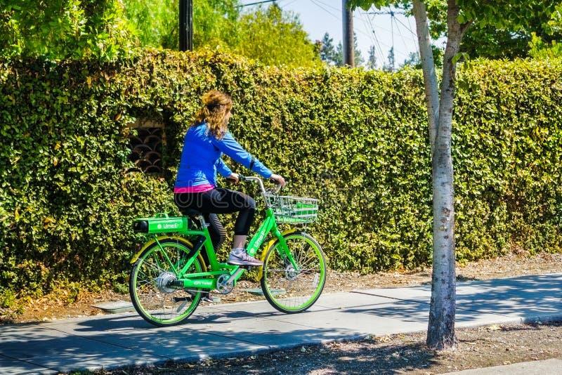 Girl riding a Lime bike on a sidewalk stock photo