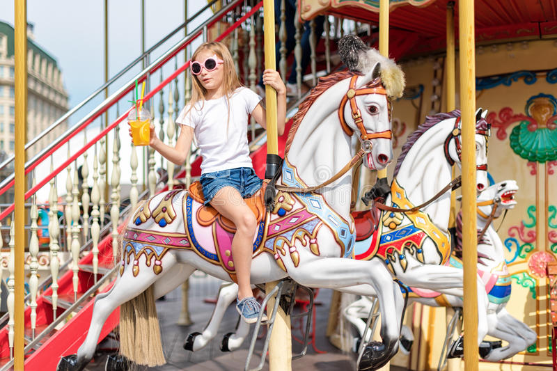 Girl riding on a merry go round. Little girl playing on carousel, summer fun, happy childhood and vacation concept stock photos