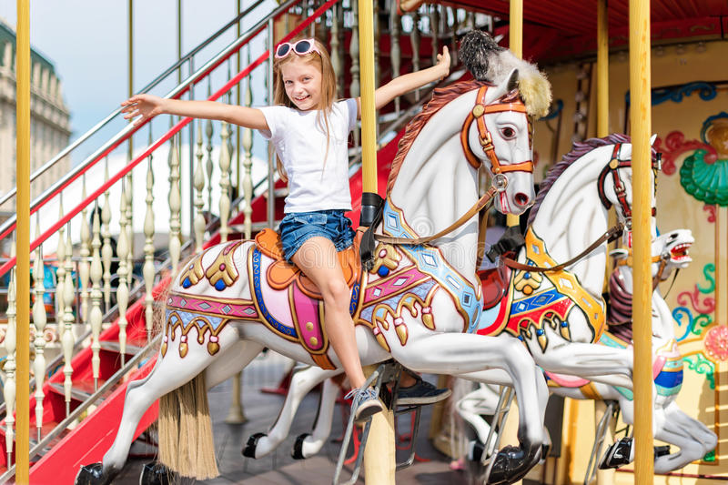 Girl riding on a merry go round. Little girl playing on carousel, summer fun, happy childhood and vacation concept.  stock image