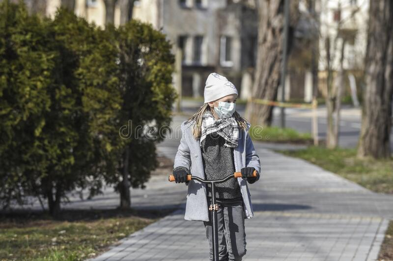 Girl riding scooter with mask stock photos
